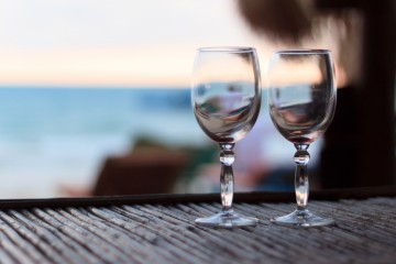 Beach evening on the sunset with two glasses